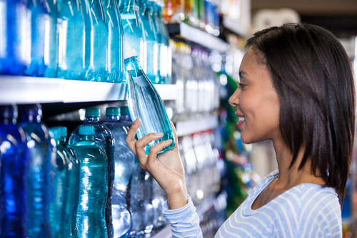 smiling-woman-buying-a-bottle-of-water-in-grocery-section-of-supermarket